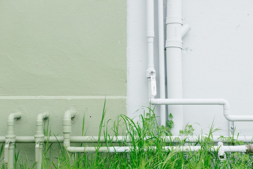 white metal water pipe near grass